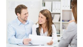 26572176-Young-couple-sitting-at-a-desk-in-the-office-of-their-agent-or-adviser-discussing-an-investment-pres-Stock-Photo_grid.jpg